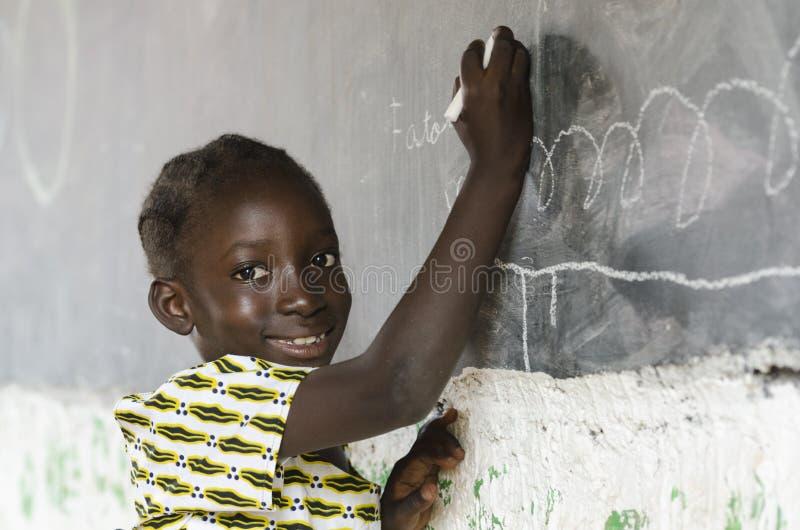 学习在黑板前面的小非洲女孩 图库摄影