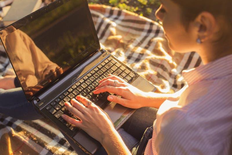 学习坐格子花呢披肩的美丽的深色的妇女键入在a 免版税库存照片