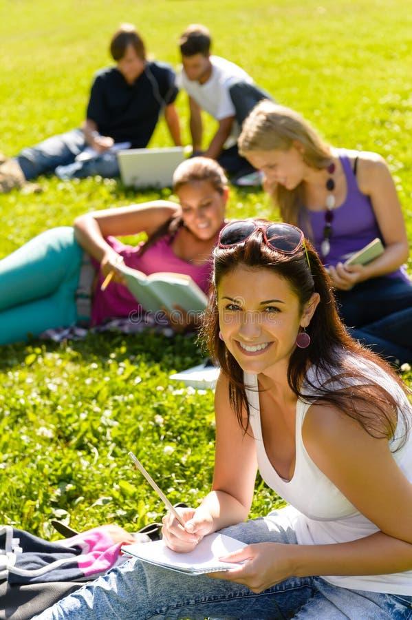 学习坐草的学员在公园 库存图片