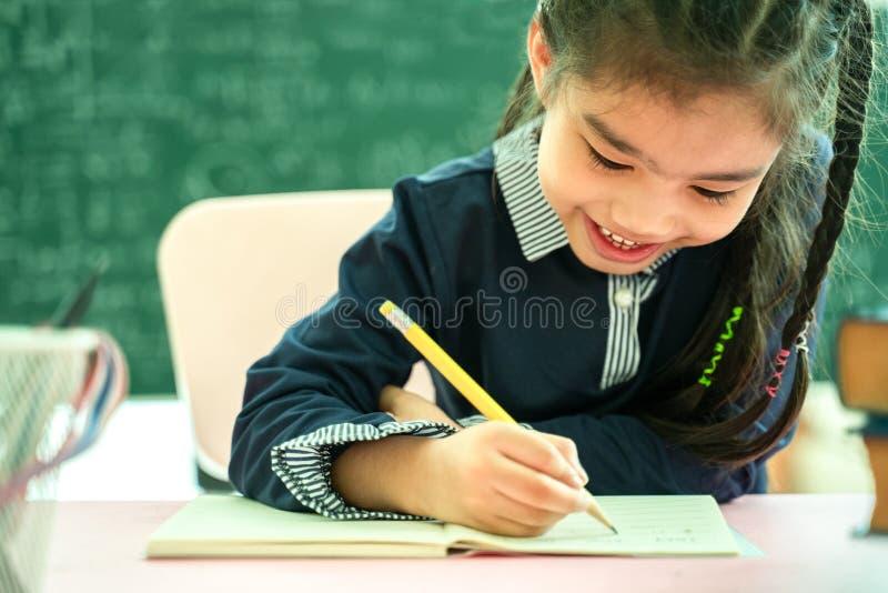 学习家庭作业的亚裔小学学生在教室 免版税图库摄影