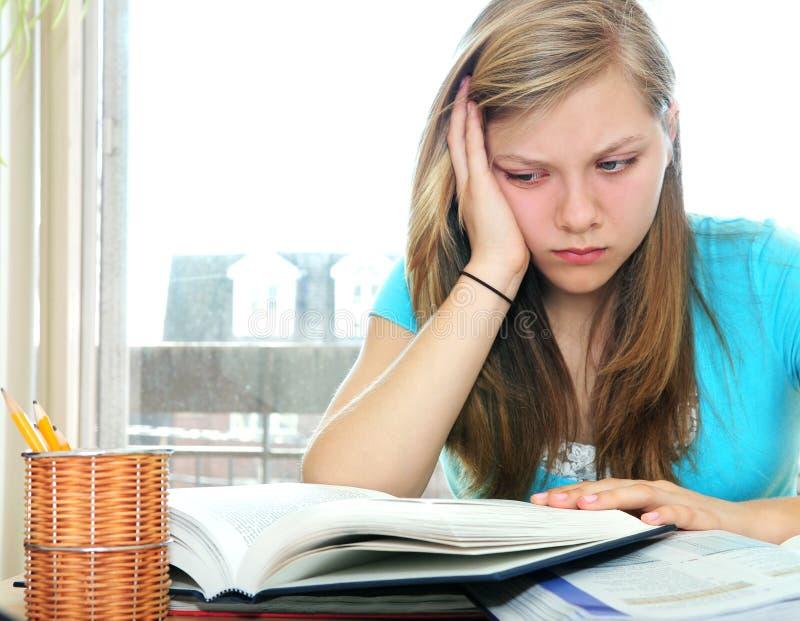 学习少年课本的女孩 免版税库存照片