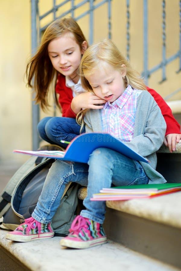 学习户外在明亮的秋天天的可爱的矮小的女小学生 做他们的家庭作业的年轻学生 小孩子的教育 免版税库存照片