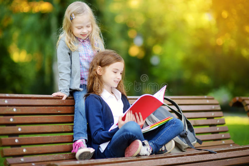 学习户外在明亮的秋天天的可爱的矮小的女小学生 做他们的家庭作业的年轻学生 小孩子的教育 库存照片