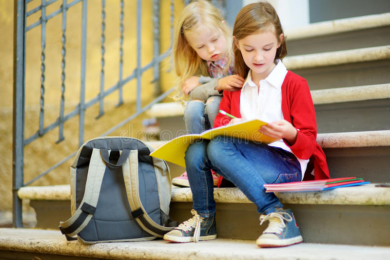 学习户外在明亮的秋天天的可爱的矮小的女小学生 做他们的家庭作业的年轻学生 小孩子的教育 库存图片