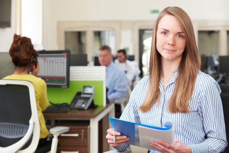 学习报告的女实业家画象在繁忙的现代办公室 图库摄影