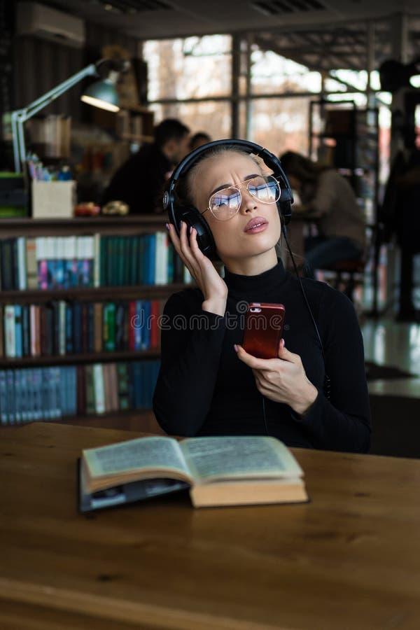 学习的大学生的画象和在有的图书馆里享受听的音乐耳机 图库摄影