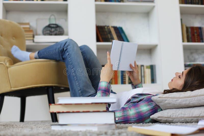 学习的学生在家,说谎在地板上反对舒适国内内部,围拢与堆书 免版税库存照片