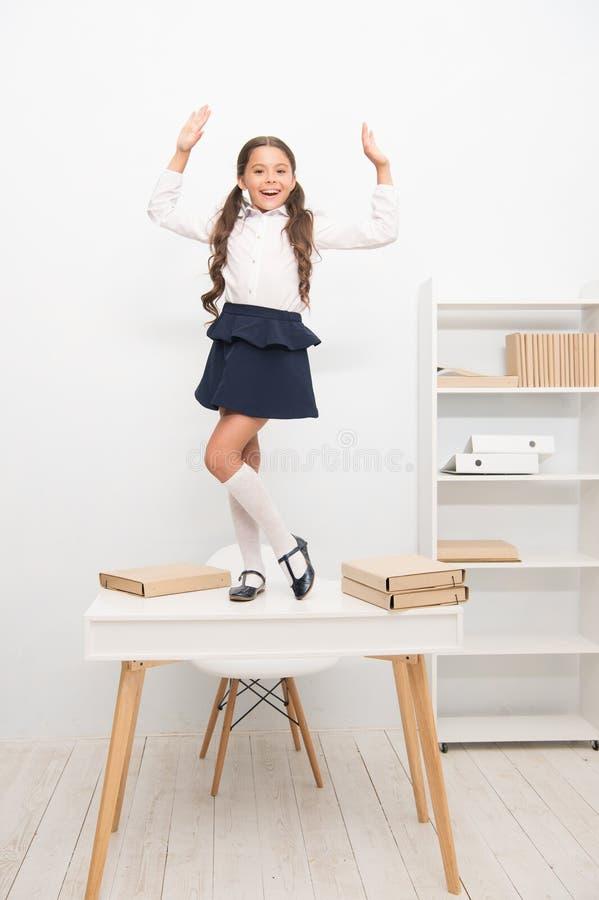 学习的学生庆祝精整,在桌上的女孩校服愉快的快乐的舞蹈 女小学生的简单的幸福 免版税库存图片