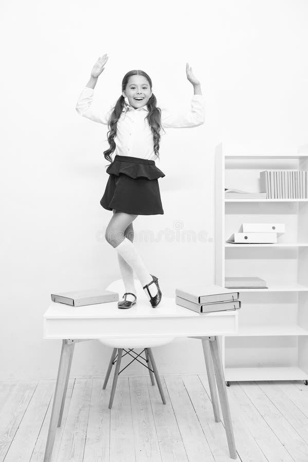 学习的学生庆祝精整,在桌上的女孩校服愉快的快乐的舞蹈 女小学生的简单的幸福 图库摄影
