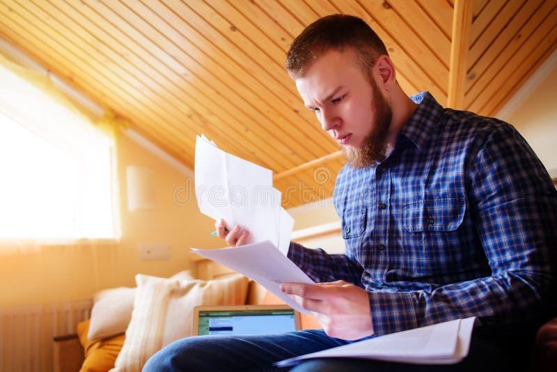 学习从家的年轻人坐拿着文件的沙发,当研究便携式计算机时 库存照片