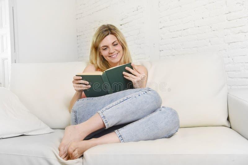 学习说谎的年轻美丽的白种人妇女阅读书舒适在看起来家庭的沙发愉快 免版税库存图片