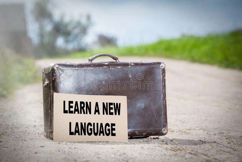 学会一种新的语言 在乡下公路的老旅行的手提箱 库存图片