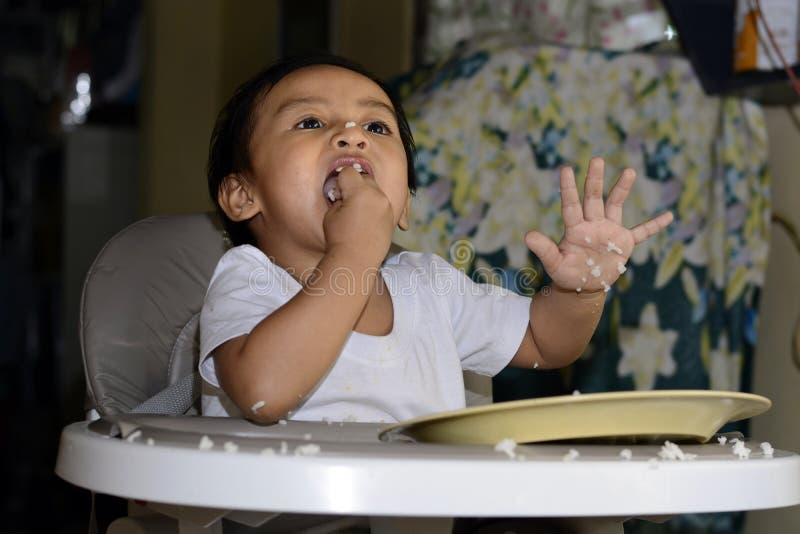 学会一1岁亚裔的男婴由匙子吃他自己,杂乱在家用餐椅子的婴孩 库存照片