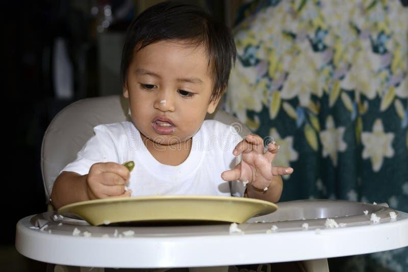 学会一1岁亚裔的男婴由匙子吃他自己,杂乱在用餐椅子的婴孩 免版税图库摄影