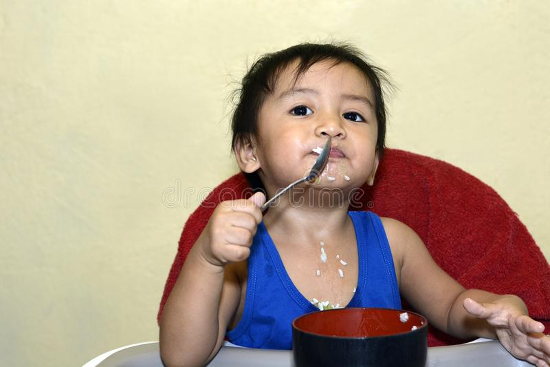 学会一1岁亚裔的男婴由匙子吃他自己,杂乱在用餐椅子的婴孩 库存图片