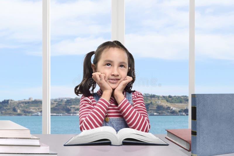 学会与书的逗人喜爱的亚裔女孩 免版税图库摄影