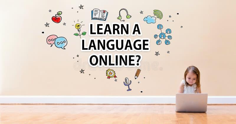 学会与使用便携式计算机的小女孩的语言网上文本 免版税图库摄影
