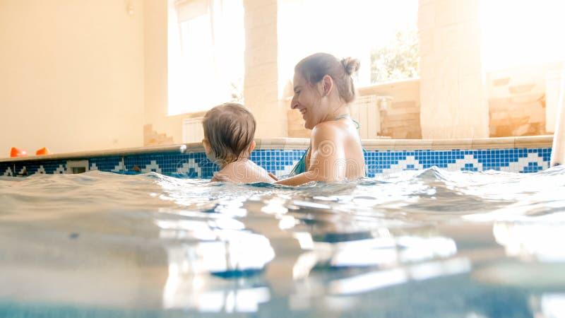 学会与母亲的愉快的微笑的小孩男孩画象游泳水池的 获得乐趣和放松在游泳的家庭 免版税库存图片