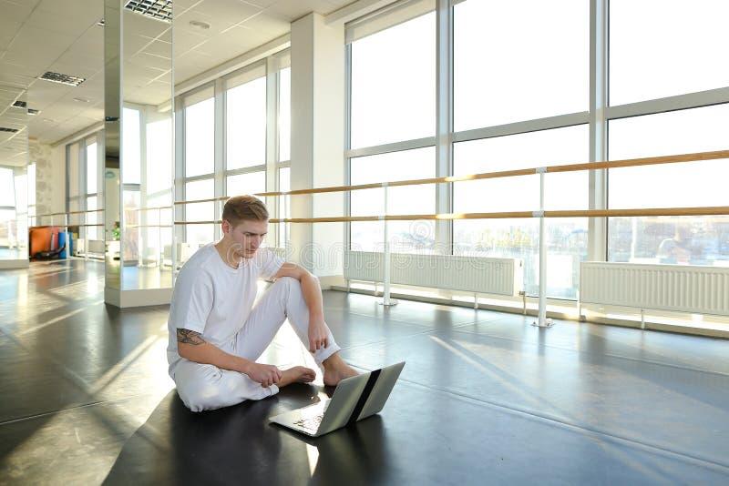 学会与膝上型计算机的男性收养新的运动在健身房 库存照片