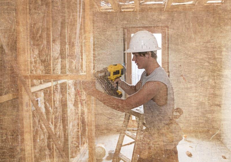 学会与钻子一起使用的防护盔甲的年轻建造者产业实习生人20s在木匠的j工业车间站点 免版税库存图片