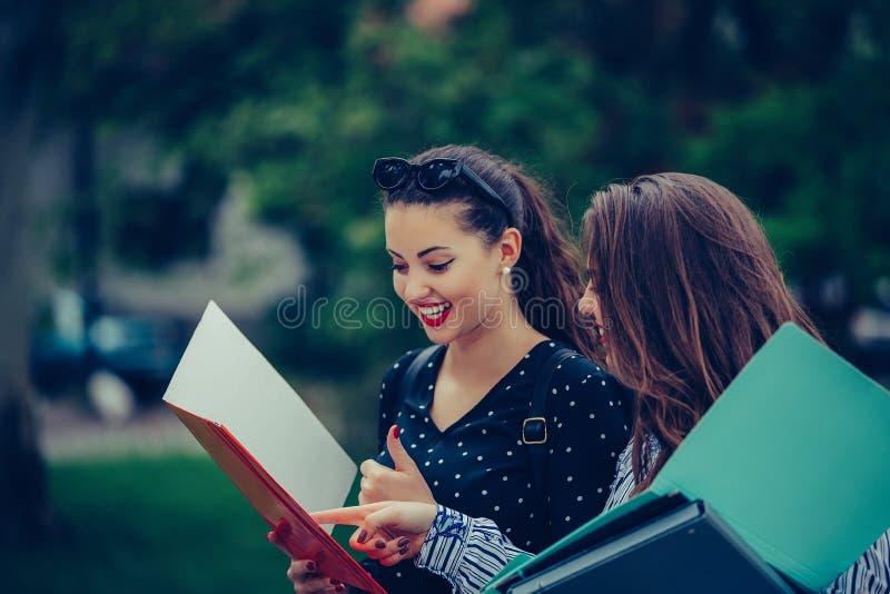 学会两个的朋友读笔记本和评论在街道 库存图片