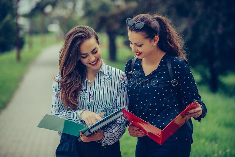 学会两名的学生读笔记本和评论在街道 免版税库存照片