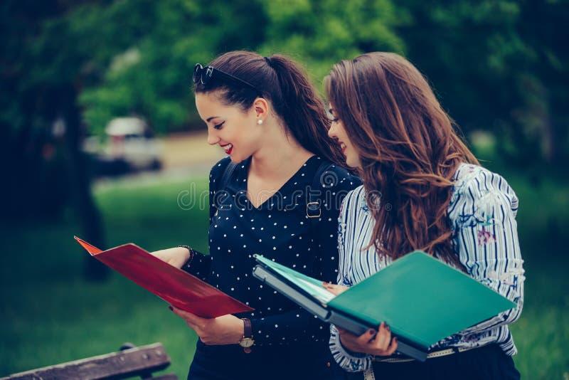 学会两名的学生读笔记本和评论在街道 库存图片