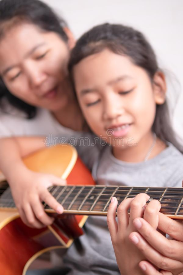 学会亚裔的女孩演奏充满幸福的音乐 免版税图库摄影