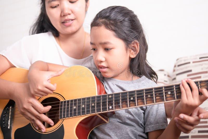 学会亚裔的女孩演奏音乐 免版税库存照片