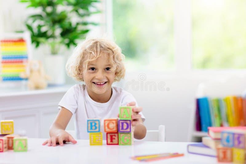 学会信件的孩子 与木abc块的孩子 免版税库存图片