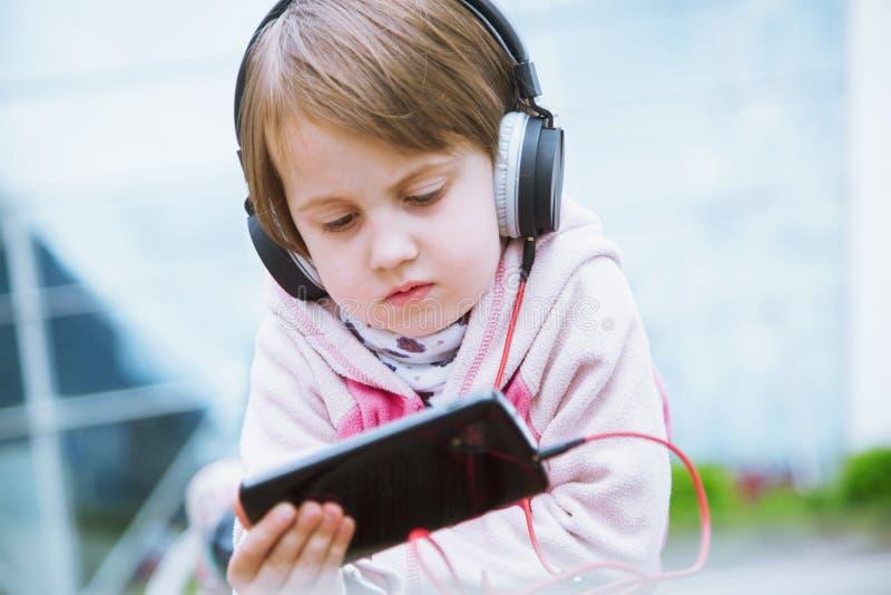 学会到处和任何时候是 使用手机的小逗人喜爱的儿童女孩观看网上电子教学录影的对学习英语 库存照片