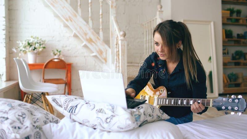 学会可爱的女孩弹有笔记本的电吉他在家坐床在卧室 免版税库存照片