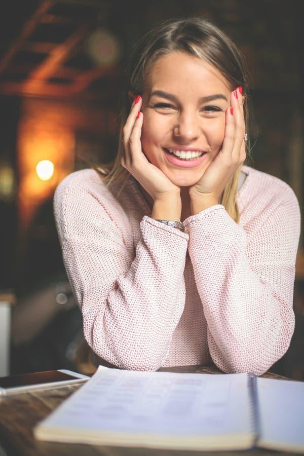 学会和看照相机的微笑的愉快的女学生 免版税库存图片