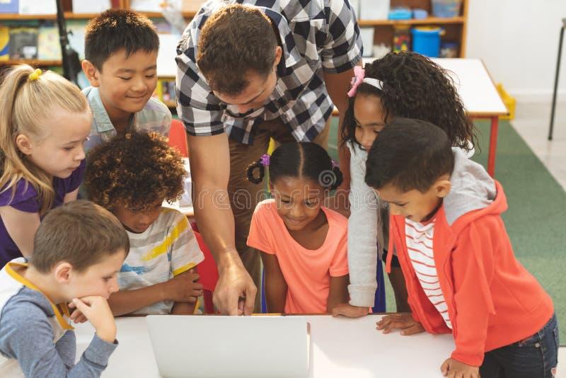 学会在他的学校孩子怎么的老师使用膝上型计算机在教室在学校 库存图片