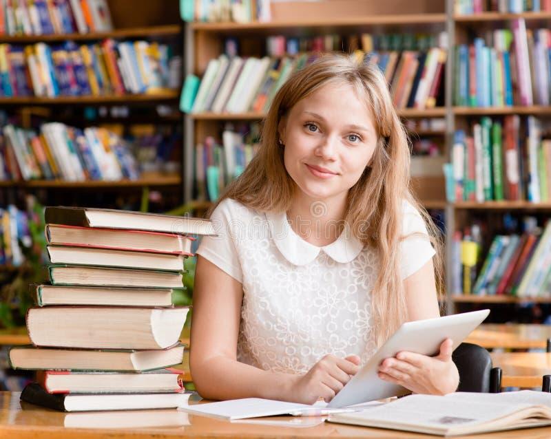 学会在图书馆里和读e书的女孩在片剂计算机上 库存图片