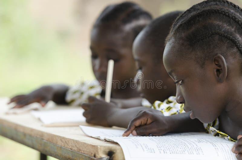 学会在学校的三个非洲孩子户外 免版税库存照片