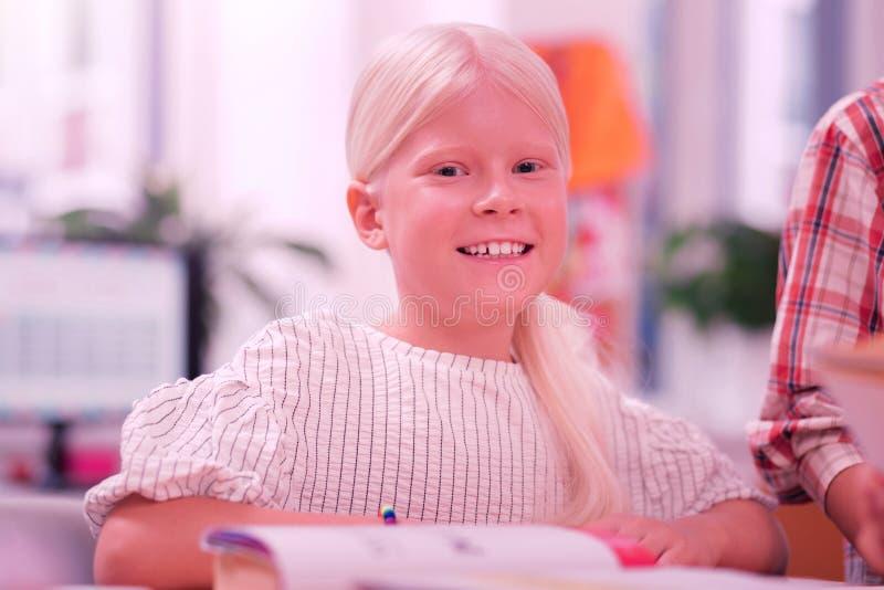 学会在学校课程的愉快地微笑的女孩 免版税库存图片