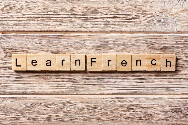 学会在木刻写的法国词 学会在桌上的法国文本,概念 免版税库存照片
