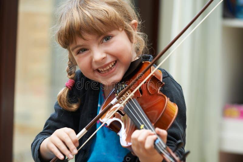 学会女孩的画象弹小提琴 免版税库存照片