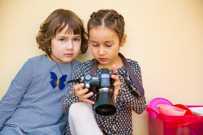 学会如何的两个小女孩使用照片照相机 免版税库存照片