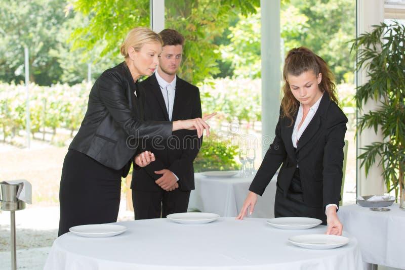 学会如何的女服务员布置桌 库存图片