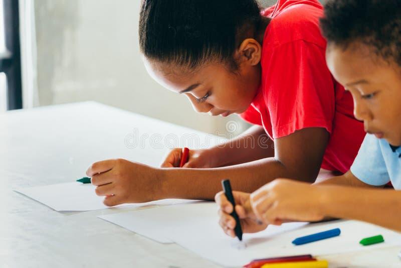 学会如何的非裔美国人的孩子画与在桌上的蜡笔 免版税库存照片