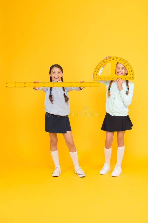 学会学校几何 有测量仪器的小学生在黄色背景 逗人喜爱学生举行 免版税图库摄影