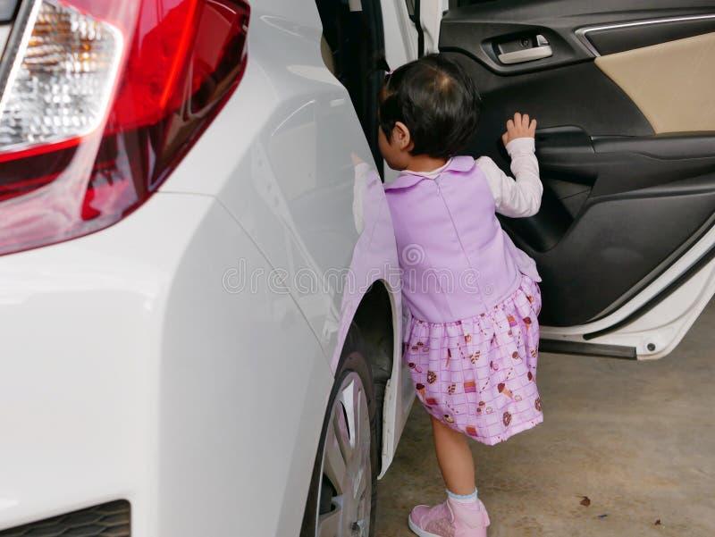 学会小亚裔的女婴进入汽车由她自己 免版税库存照片