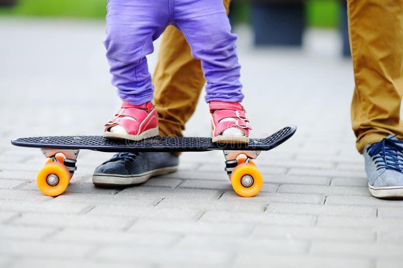 学会小孩的女孩踩滑板与她的父亲关闭 库存照片