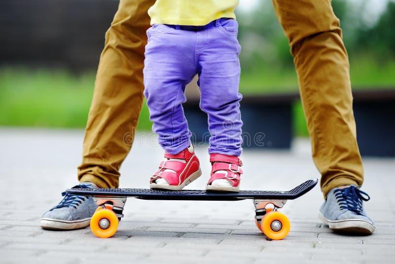 学会小孩的女孩踩滑板与她的父亲关闭 免版税库存照片