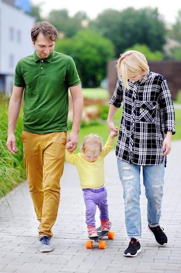 学会小孩的女孩踩滑板与她的年轻人做父母户外 免版税库存图片