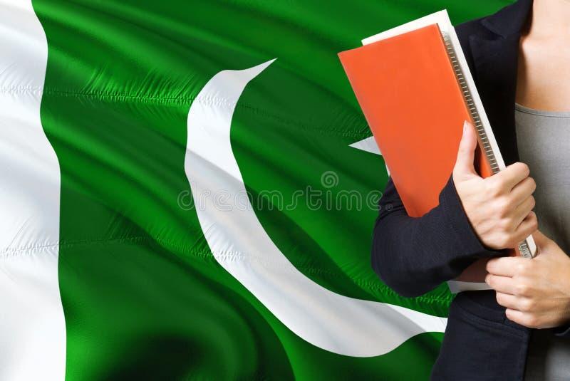 学会巴基斯坦语言概念 与巴基斯坦旗子的年轻女人身分在背景中 拿着书,桔子的老师 库存图片