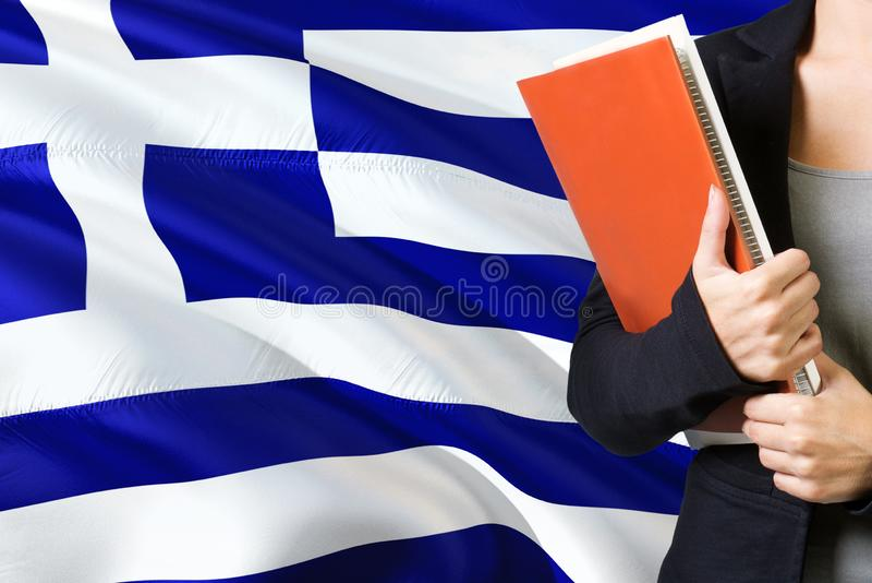 学会希腊语言概念 与希腊旗子的年轻女人身分在背景中 拿着书,橙色空白的老师 免版税库存图片