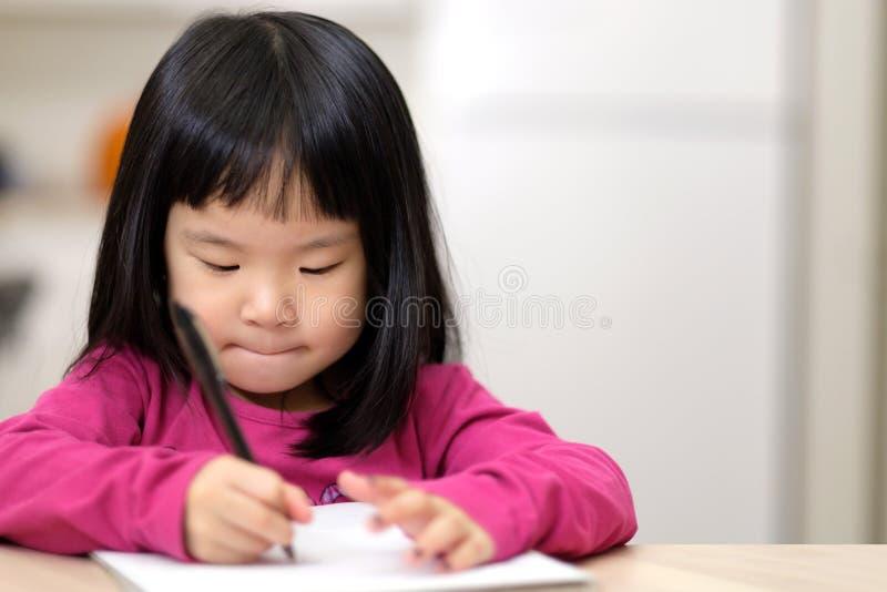 学会年轻矮小的亚裔的女孩写 免版税库存照片